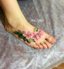 ветка с цветами тату на ступне у девушки добавлено Slava Jangle