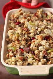 a small cerole dish filled with sausage cranberry pecan stuffing