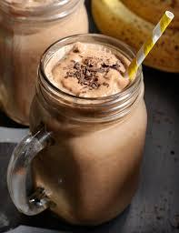 chocolate banana protein shake in a gl mug with chcocolate shavings on top