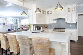 white kitchen with chrome pendant lights blue backsplash dark hardwood flooring and wicker breakfast