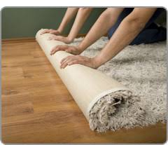 An area rug being rolled out on a hardwood floor