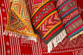 pile of north african rugs in red orange brown shades morocc stock