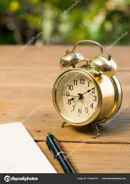soft focus of blank notebook with vintage alarm clock and black pen on wood table the background is green from tree and light bokeh photo by prot56