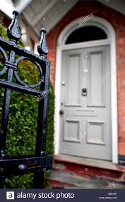 house front door open. An Open Front Gate Leading To A Hedge And Grey Door Of Terraced Victorian House. House