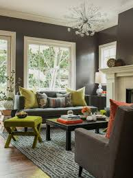 living room grey sofa and cushions also black wooden table and green ottoman on grey