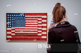 stock photo tourist taking a photo with her smartphone of the painting by the american artist jasper johns entitled three flags whitney museum of