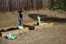 this dad gets assistance from his daughter to build a raised bed garden in which to
