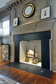 gray washed wood paneled wall and fireplace with gray washed molding and dental trim the fireplace features a black stone surround and white herringbone