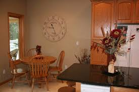 minimalits kitchen design with white large decorative kitchen wall clocks and wooden dining set near