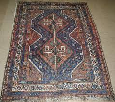 a qashqai rug early 20th century the indigo field with double red medallion pole similar spandrels within ivory border