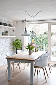 dining room chairs painted white. a relaxing dining room with industrial pendant lights over the table, brick walls and potted flowers - home decorating magazines chairs painted white