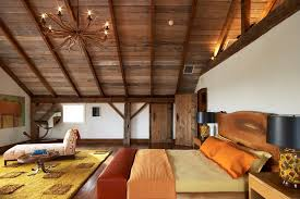 the barn s master bedroom is a loft like space with a gabled ceiling a twig chandelier hangs above a rustic headboard made from a single wood slab