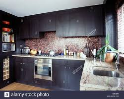 black and stainless kitchen black stained oak units in modern kitchen with mosaic tiled splashback and stainless steel oven