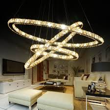 unique crystal pendant light in modern lighting design in white themed living room and white leather sofa and ottomans over laminate floor facing wide flat
