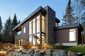This modern lake house in Canada has an exterior clad in wood, stone, and
