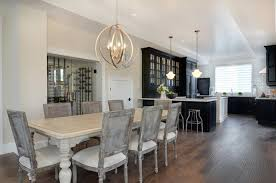 open floor plan living features sphere chandelier over antique white dining table surrounded by gray cane back chairs restoration hardware vintage french