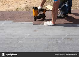 Roofer Builder Worker With Nailgun Installing Asphalt