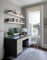 chic office features stacked white floating shelves over black and white desk accented with brass ring pulls topped with art deco table lamp paired with
