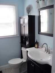 corner design medicine cabinets painted dark brown with soft blue wall  bathroom decor and single windows