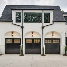 With garage door lighting over each door and plantings in between ...