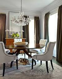 formal round dining table with upholstered chairs and a crystal candelabra chandelier ashley goforth design