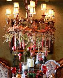 beautiful chandelier with hanging red ornaments vintage ribbon and evergreens