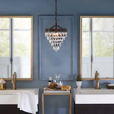 bathroom with blue walls a crystal chandelier and brass accessories