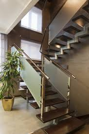 A modern staircase with frosted glass railing panels and floating wooden  treads. Do you like