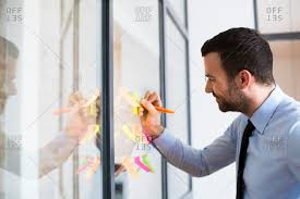 businessman in office writing on adhesive note on glass wall stock photo offset