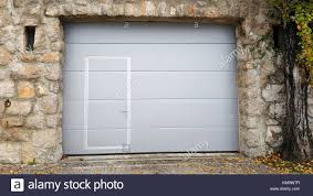 Modern Roll Up Metal Garage Doors With Integrated Smaller Inside Traditional Stone Wall Frame Two Openings Large Old Tree And Small Rusted