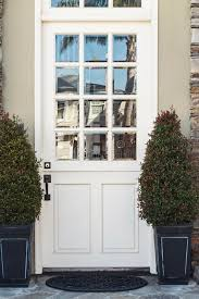 White Front Door To Modern Home Flanked By Plants Stock Photo