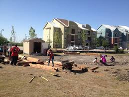 volunteers help build the large community garden at sutton oaks on may 3 photo by