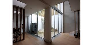 internal basement view of the double height lightwell using slim framed sliding glass doors