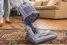 shark navigator vacuum being pushed across a rug in front of a couch