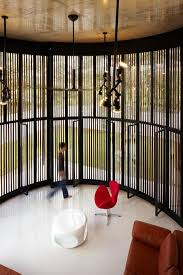 Curved and Stacking Louvered Glass Doors Surround Room in Voila House