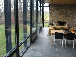 remarkable glass wall and door with black frame also gray floor stair case plus exposed stone wall