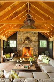 exposed wooden ceiling beams above the stone mantel fireplace plus sectional sofa and rattan hammock
