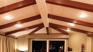 cathedral ceiling with up lighting between exposed beams in open plan living area