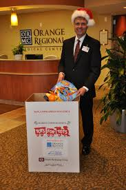 2011 orange regional s executive director of public relations and marketing rob lee places a gift in the toys for tots donation bin