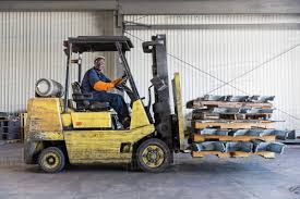Black Worker Driving Forklift In Factory Stock Photo Dissolve