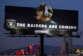a raiders billboard shows a picture of the team s new head coach jon gruden at the