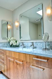 carrera marble bathrooms basket weave backsplash mirrors wall lamps wide sink double faucets wooden cabinets blue