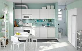 white kitchen cabinet with integrated dishwasher and white shelf unit also white dinette set
