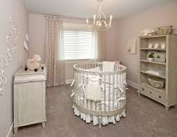 round crib under tiny baby nursery chandelier near window plus shutter on pastel wall paint and floating shelves on large carpet plus cute dolls decor