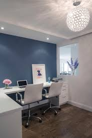 Modern Home Office Features Fireplace Pinterest This Modern Home Office Features White Desk With Two Leather Chairs Positioned In Front Of Bluegray Accent Wall Section The Enclosing