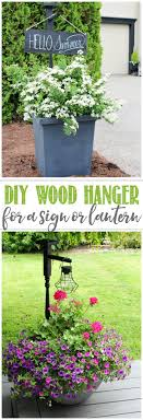 diy wooden holder in a planter used to hang a wooden sign or hanging solar lantern
