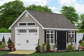 a small standalone garage lined with little shrubs has a white garage door to match the