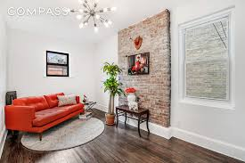 This gut-renovated UWS apartment showcases exposed brick on the fireplace  wall.