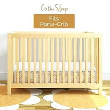 portacrib crib with sunflower rug and white paint wall for modern nursery