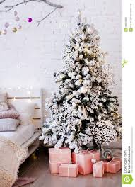 tree decorated with large wooden snowflakes near the bed